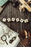 Top view of arranged wooden blocks in travel word with map, retro photo camera, bag and magnifying glass on dark wooden tabletop stock photography