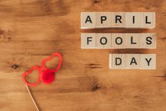 Top view of arranged wooden cubes in april fools day lettering with party eyeglasses and clown nose on wooden tabletop, 1 april. Holiday concept stock photography