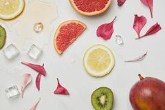top view of arrangement of fresh exotic fruits, ice cubes and flower petals on white surface stock image