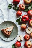 Top view of arrangement of piece of apple pie on plate and fresh apples. On white tablecloth royalty free stock photo
