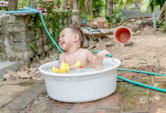 Top view Asian baby boy outdoor bathing in the white bathtub . H Stock Photos