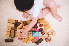 Top view asian child building playing toy blocks wood. Indoors room royalty free stock photo