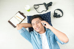Top view of asian man lying on the floor with laptop, camera, ta Stock Photos