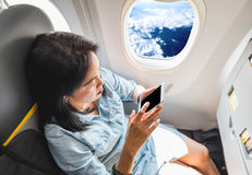 Top view of Asian Woman sitting at window seat in airplane and t Stock Photos