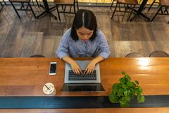 Top view of woman typing on laptop on wooden table stock photography