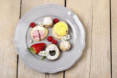 Top view of assorted cookies and fruits on grey ceramic plate Royalty Free Stock Images