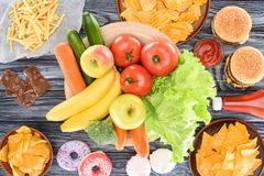 Top view of assorted junk food and fresh fruits with vegetables on wooden table royalty free stock photography