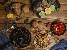 Top view of assorted seafood and baked fish with bread and tomatoes Royalty Free Stock Images