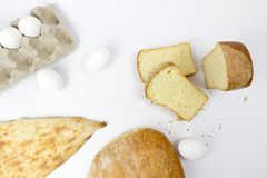 Top view of assortment of different kind of cereal bakery: bread, croissants, buns isolated on white woodden background stock photo