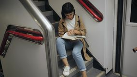 Activity in train. Top view on attractive brunette student girl is reading a book sitting on stairs of double decker train car during her commute trip stock video
