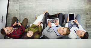 Top view of attractive girls and guy using a laptop, looking at camera and smiling while sitting on the floor. Stock Image