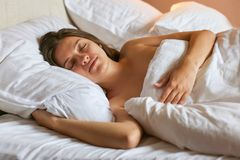 Top view of attractive young woman sleeping well in bed hugging soft white pillow. Teenage girl resting, good night sleep concept. Lady enjoys fresh soft royalty free stock image
