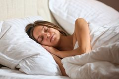 Top view of attractive young woman sleeping well in bed hugging soft white pillow. Teenage girl resting, good night sleep concept. Lady enjoys fresh soft stock photography