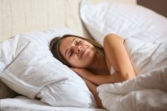 Top view of attractive young woman sleeping well in bed hugging soft white pillow. Teenage girl resting, good night sleep concept. Lady enjoys fresh soft stock photos