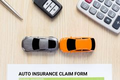 Top view of auto insurance claim form with car toy crash on wood. En desk Royalty Free Stock Photos