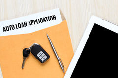 Top view of auto loan application in envelope with car remote key, pen and tablet.  stock image