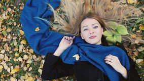 Top view of autumn blond woman lying over leaves royalty free stock photo