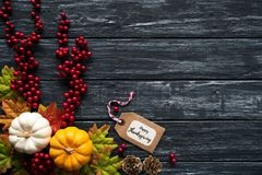 Top view of Autumn maple leaves with Pumpkin and red berries on old wooden backgound. stock photo