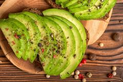 Top view of avocado sandwiches with cutted rye bread and sprinkl. E with pepper on wooden background, healthy lifestyle Stock Images