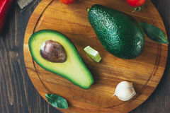Top view of avocado standing on wooden board surrounded by vegetables. Royalty Free Stock Images