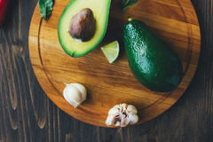 Top view of avocado standing on wooden board surrounded by vegetables. Stock Images