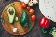 Top view of avocado standing on wooden board surrounded by vegetables. Royalty Free Stock Photography