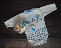 Top view of baby clothes and blue baby booties Stock Photo. Top view of baby clothes and blue baby booties stock photos