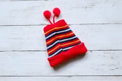 Top view of baby red snow cap on white  wooden background.  Royalty Free Stock Images