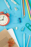 Top view back to school concept. Creative flat lay top view back to school concept with alarm clock, color school and office supplies on bright turquoise paper stock photo