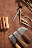 Artisan Leatherwork. Top view background of leatherworking tools lying on wooden table in artisan atelier, copy space royalty free stock images