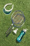 Top view of badminton equipment, water bottle and cap. On green grass stock photo