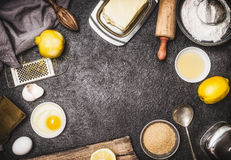 Top view of bake preparation with kitchen tools and ingredients for cake or cookies : lemon , flour, egg, raw sugar and butter on. Dark rustic kitchen table Royalty Free Stock Photography