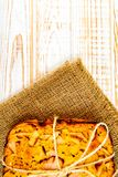 Top view of baked pie with apples on sackcloth on a white wooden background. Rustic style. Fresh bakery. Top view of baked pie with apples on sackcloth on a stock photography