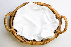 Top view on bakery basket with napkin. Top view, bakery basket with napkin on the white tablecloth Royalty Free Stock Photo