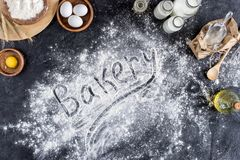 Top view of bakery lettering made of flour and various ingredients for baking. On dark surface stock photo