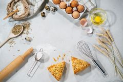 Natural ingredients for baking. Top view of baking ingredients and some pieces of cake on kitchen table isolated on grey backround Stock Image