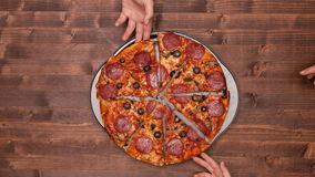 Top view of baking a pizza with hands taking slices stock video
