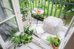 Balcony with plants, pouf a table with breakfast. Top view of a balcony with plants, pouf a table with breakfast stock photography