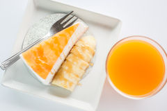 Top view of banana caramel crepe cake and orange juice on white Royalty Free Stock Images
