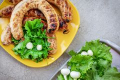 Top view of barbecue sausages in a yellow plate and an aluminum tray with green vegetation.  royalty free stock image