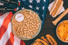 Top view of baseball ball on plate with peanuts, baseball bat, glove, hot dog and beer bottles. On american flag royalty free stock image