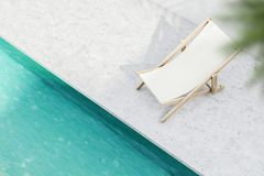 Top view of a beach chair near pool. Top view of a white beach chair standing near a resort or private pool with blue green water. Concept of rest and relaxation Stock Photography