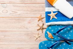 Top view of Beach flat lay accessories. sunscreen bottle with seashells, starfish, towel and flip-flop on wooden board background. With copy space royalty free stock image