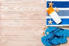 Top view of Beach flat lay accessories. sunscreen bottle with seashells, starfish, towel and flip-flop on wooden board background. With copy space stock photos