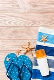 Top view of Beach flat lay accessories. sunscreen bottle with seashells, starfish, towel and flip-flop on wooden board background. With copy space stock image