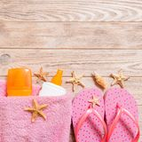 Top view of Beach flat lay accessories. sunscreen bottle with seashells, starfish, towel and flip-flop on wooden board background. With copy space stock photo