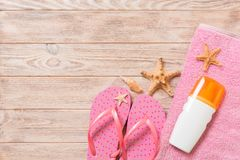 Top view of Beach flat lay accessories. sunscreen bottle with seashells, starfish, towel and flip-flop on wooden board background. With copy space royalty free stock photos
