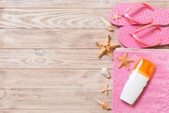 Top view of Beach flat lay accessories. sunscreen bottle with seashells, starfish, towel and flip-flop on wooden board background. With copy space stock images