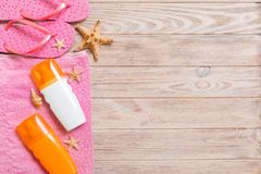 Top view of Beach flat lay accessories. sunscreen bottle with seashells, starfish, towel and flip-flop on wooden board background. With copy space royalty free stock photo