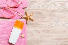 Top view of Beach flat lay accessories. sunscreen bottle with seashells, starfish, towel and flip-flop on wooden board background. With copy space stock photography